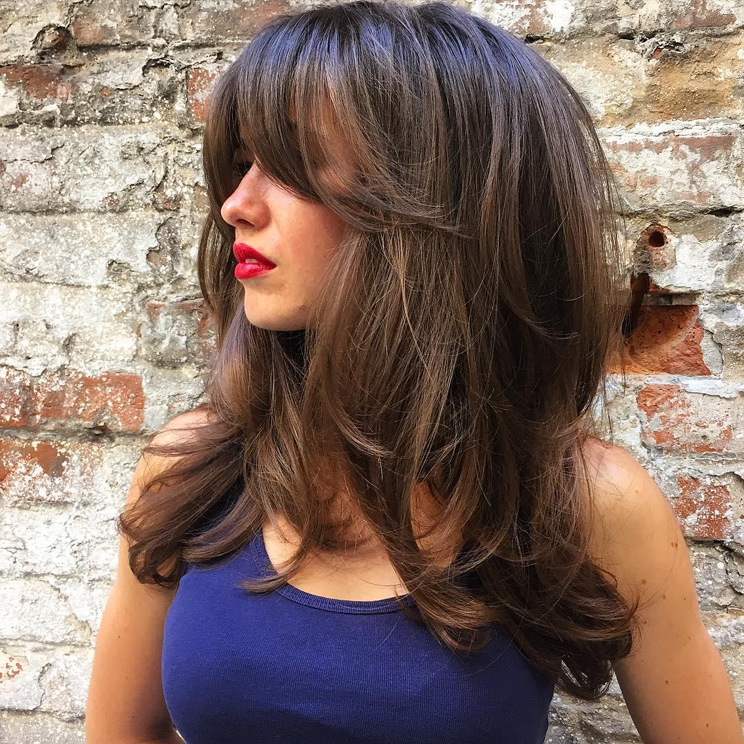 Taglio scalato capelli castani con frangia lunga