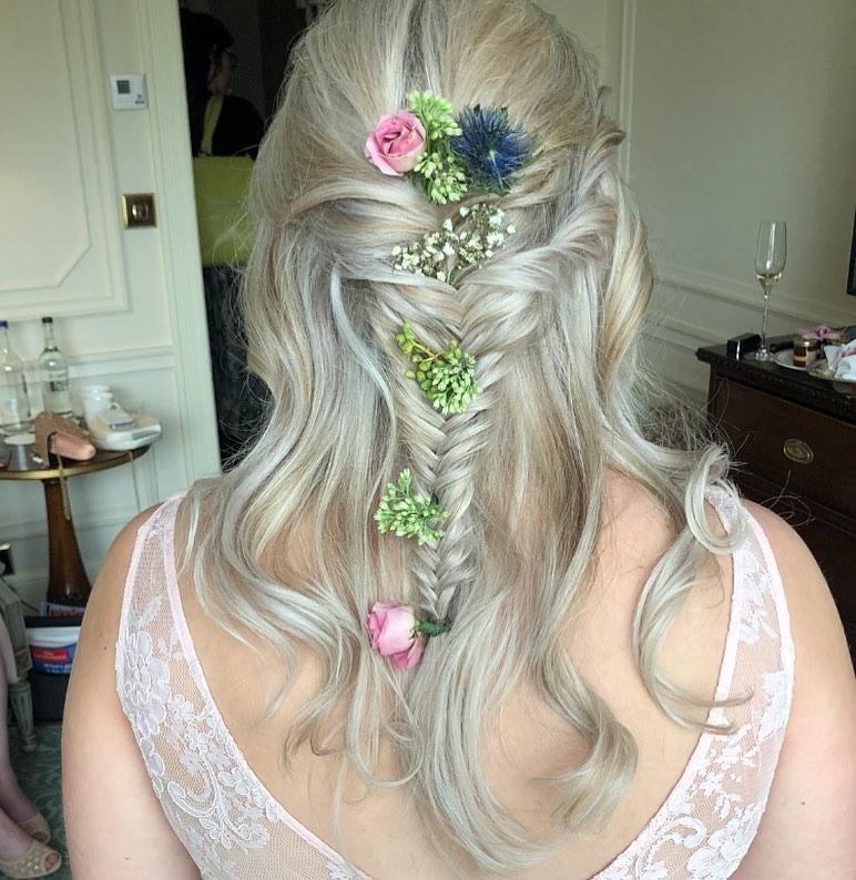 acconciatura da sposa boho chic con capelli semi raccolti in una treccia a spina di pesce e fiori freschi