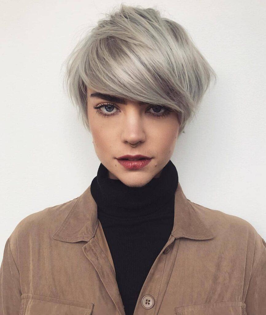 capelli corti con lungo ciuffo laterale, biondo cenere quasi grigio