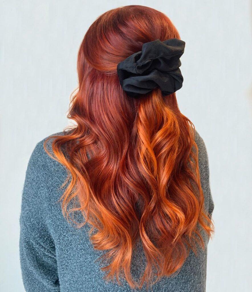 lunghi capelli mossi con balayage rosso rame, semi raccolti con elastico in tessuto in stile anni '80-90