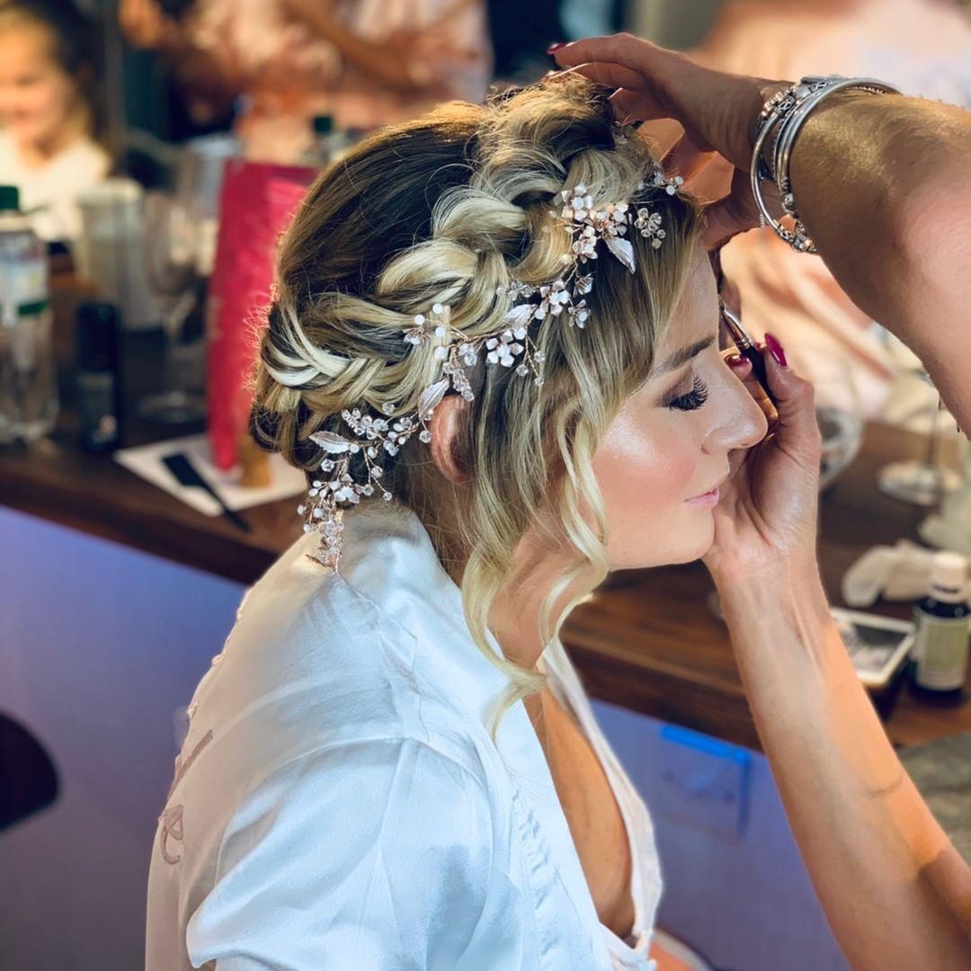 treccia a corona con accessorio bucolico e boccoli lasciati liberi sul davanti, perfetta acconciatura da sposa