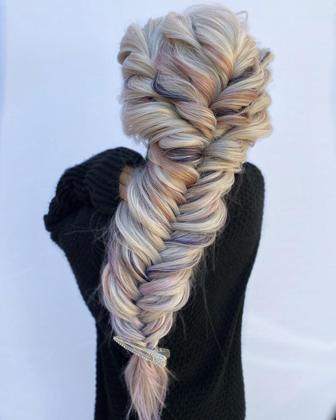 treccia a spina di pesce su capelli biondi con ciuffi rosa e viola