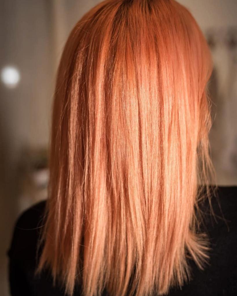 Capelli arancioni media lunghezza scalati con styling liscio