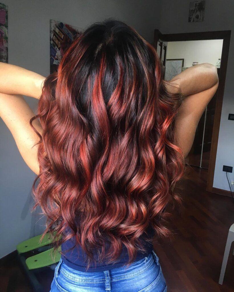 Balayage rosso luminoso su capelli lunghi e mossi