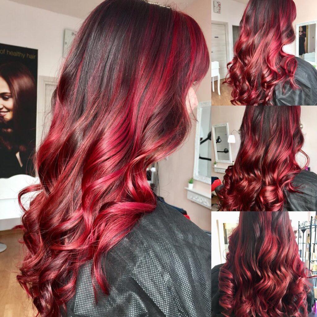 Balayage rosso acceso su capelli lunghi e con morbide onde