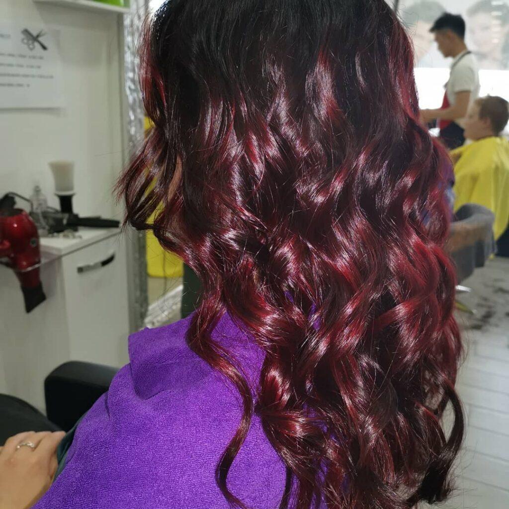 Balayage rosso mogano su capelli scuri e ricci