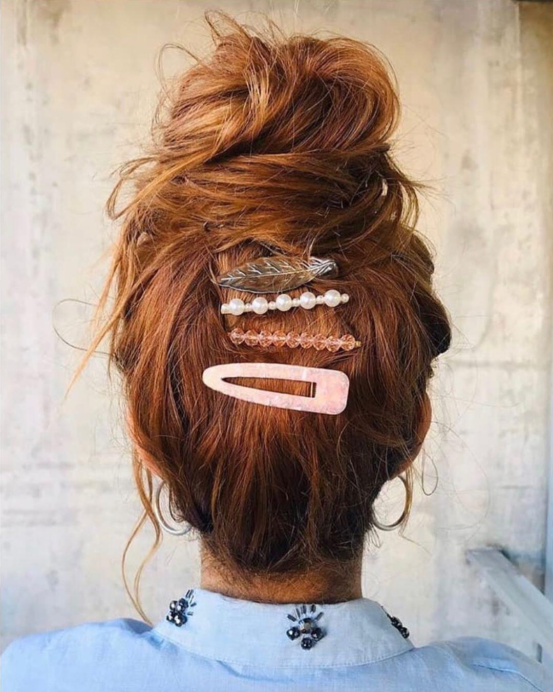 capelli castani ramati con chignon alto e messy e fermagli in stile boho chic