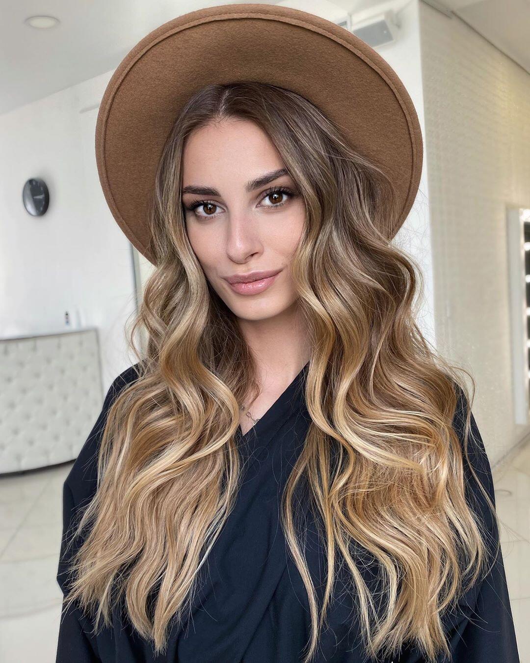 lunghi capelli castani con balayage biondo e styling mosso
